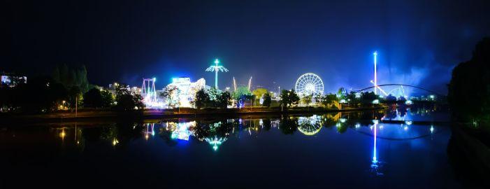Изображение: Уличный фестиваль со светящимися аттракционами и светящимся дьявольским колесом.